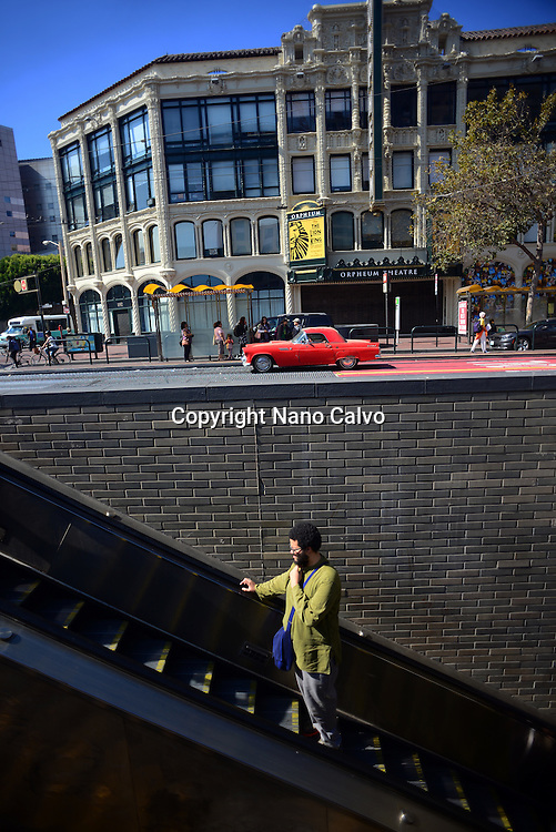 Young man in electric stairs at Market Street, San Francisco.