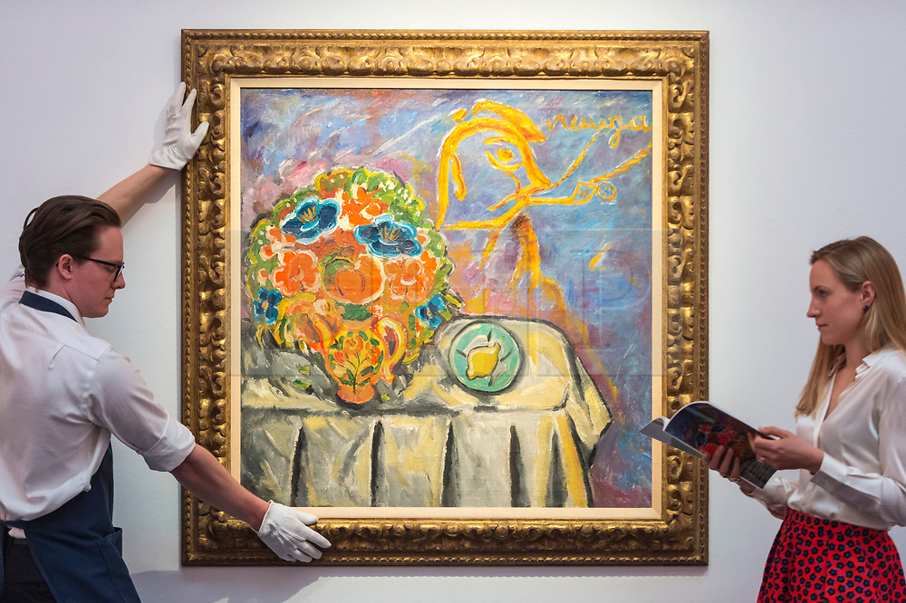 """© Licensed to London News Pictures. 31/05/2019. LONDON, UK. A technician and staff member with """"Still Life"""" by Mikhail Fedorovich Larionov (Est. GBP 1-1.5m) at a preview of works from the upcoming sale of Russian Pictures, Works of Art, Fabergé & Icons Sales at Sotheby's, New Bond Street, on 4 June 2019.  Photo credit: Stephen Chung/LNP"""