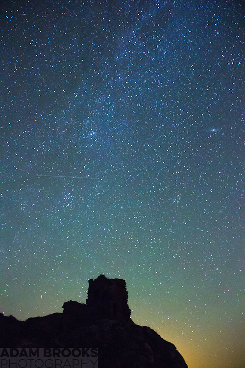 The Milky Way dust lane with Kinbane Castle in the foreground. The Andromeda Galaxy can be seen about two thirds up on the right hand side and a satellite trail streaking across the Milky Way just below the H & Chi persei double open Cluster.