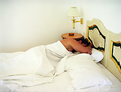 man without a shirt sleeping in a bed