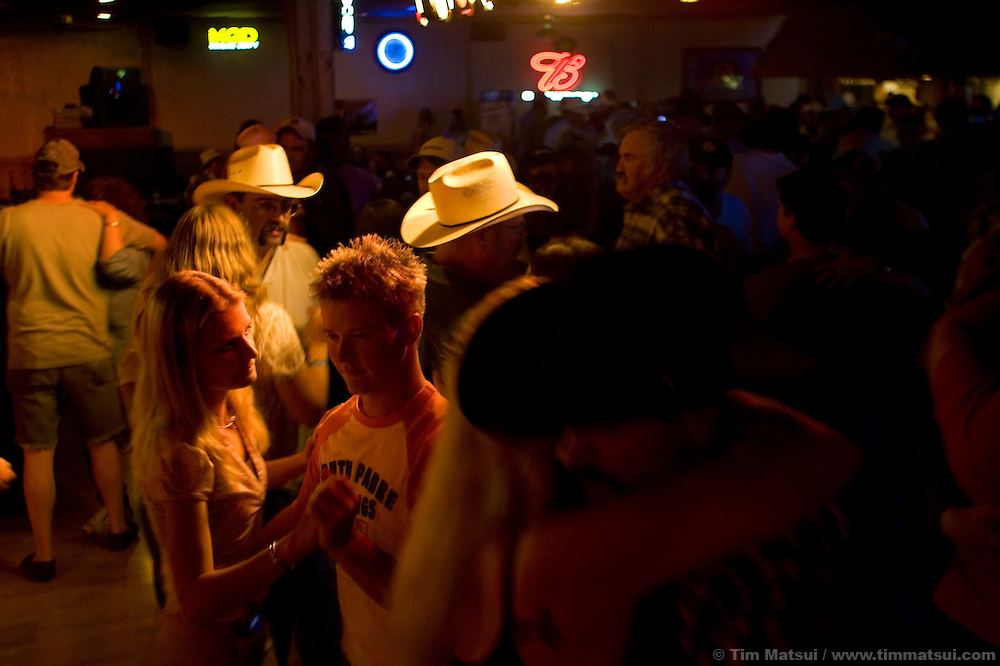 ROCK SPRINGS, WY - Locals, including 'seasonal' gas field workers, dance at the Satellite to live country music in Rock Springs, Wy., on August 6, 2005. A boom in natural gas drilling and completion has brought an influx of workers, some of whom  choose to move to local towns like Rock Springs or Pinedale, but many others are seasonal or contract employees who will do shifts that may be 20 days on and 10 days off during which they will return home to places like Oklahoma or Texas. Crew 187, a 'Special Services' team for Haliburton, dominated the night's crowd at the Satellite. Haliburton has committed a multi-million dollar services yard to Rock Springs from which it will support gas drilling operations in the western Rockies. Crew 187 is moved where ever Haliburton has an employee shortage so for the last year they have been boarded at the Rock Springs Holiday Inn as Haliburton's business has been booming in the area.