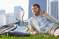 Man lying on lawn in park talking on mobile phone
