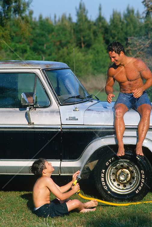 Boy spraying water at a shirtless man sitting on a truck out in the country
