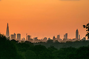 UNITED KINGDOM, London: 13 May 2015 The London skyline stands in front of an orange sky before sunrise from Richmond Park, London this morning. Although it was a cold start to the day, temperatures are set to get up to 20C. Rick Findler  / Story Picture Agency