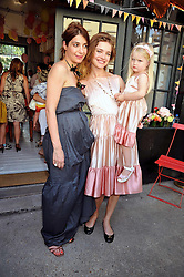 Left to right, party host Eva Karayiannis, NATALIA VODIANOVA and her daughter NEVA PORTMAN at the 10th anniversary party of the store Caramel, Ledbury Road, London W11.  The party was held in association with the Naked Heart Foundation - a charity set up by model Natalia Vodianova.