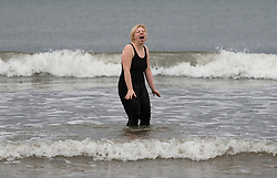 © Licensed to London News Pictures. 01/01/2012..Saltburn Beach, England..Brave souls plunge into the cold North Sea as they take part in the annual New Year Day dip at Saltburn in Cleveland...The dip is held, primarily, to raise money for the Saltburn Animal Rescue Association or SARA...The Association was formed in 1995 by a small group of animal lovers who sought to help animals in need...Their aim is to help as many animals as possible by placing them into foster homes and attending to their veterinary care until responsible caring homes can be found....Photo credit : Ian Forsyth/LNP