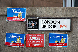 © Licensed to London News Pictures. 03/06/2018. London, UK. Posters which read 'One Year Later, London More United Than Ever' on London Bridge as flowers are laid and a minute's silence is held to mark the first anniversary of the London Bridge and Borough Market terror attack. Photo credit: Rob Pinney/LNP