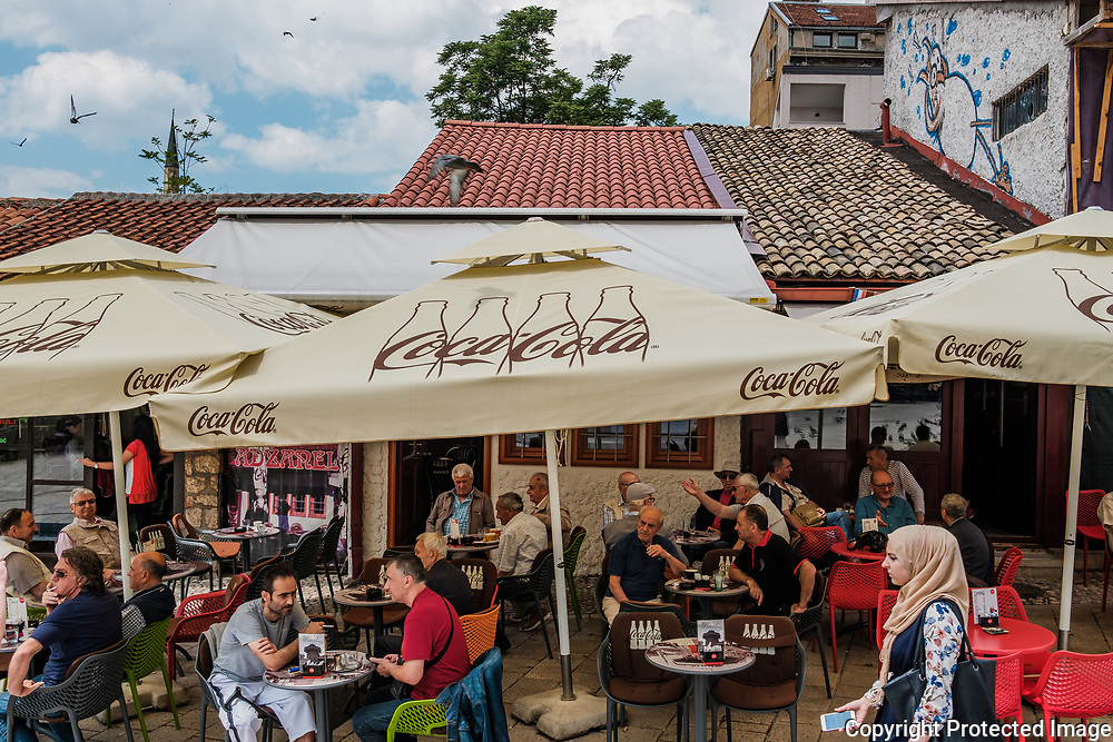 A muslim woman walks past a cafe crowded with men. Cafe culture is extremely prominent in Sarajevo. People, mostly men, can be seen idly chatting and drinking coffee day and night.