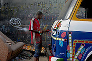 A young man paints a Rapide (mini bus) on the street in Dakar, Senegal.
