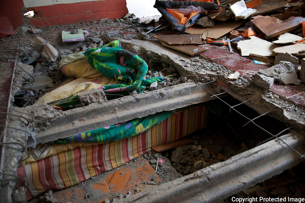 Mattress of child's bed found under the cement in an apartment building destroyed from the earthquake in Constitución, Chile