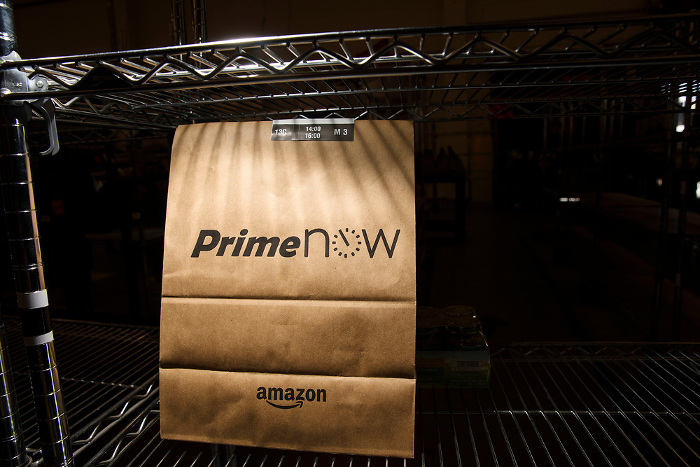 An Amazon Prime Now shopping bag awaits delivery at the Amazon.com Inc. Prime Now fulfillment center warehouse on Monday, March 27, 2017 in Los Angeles, Calif. The warehouse can fulfill one and two hour delivery to customers. Complex supply chains such as Amazon's and e-commerce trends will impact city infrastructure and how things move through cities. © 2017 Patrick T. Fallon