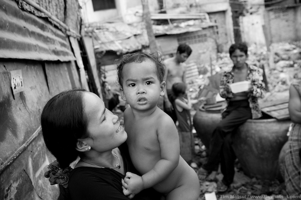 """Prostitute Srey Leat holds a baby at home in a slum where the non governmental organization """"Acting for Women in Distressing Situations"""" (AFESIP), conducts outreach and provides services in Phnom Penh, Cambodia. The permanent structure, a decaying four story building known simply as 'The Building', was built in the 1960's as transitional housing and now hosts a shantytown where many of the city's poor live, including many prostitutes, and is believed to have the highest rate of HIV infection in the city. AFESIP hands out free condoms, instructs prostitutes on HIV prevention, and conducts outreach in case the prostitutes need medical services, choose to leave their profession, or can report on cases of sex trafficking. AFESIP offers housing, education, training, and counseling for women who are victims of sex trafficking, worked as prostitutes, or are escaping domestic violence. Founded by Somaly Mam, who herself was once a prostitute and victim of trafficking and domestic abuse, AFESIP has three facilities in Cambodia and works with other NGO's to provide long term care for the women."""