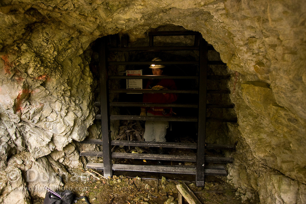Geologist and mining engineer Greg Graham inspects a bat gate at the entrance to the abandoned Gold Stake gold mine. The gate is designed to allow bats to fly in and out of the mine interior while keeping human visitors and other large animals excluded. Greg is opening the gate for a bat survey by biologists. Coleville National Forest, Washington.