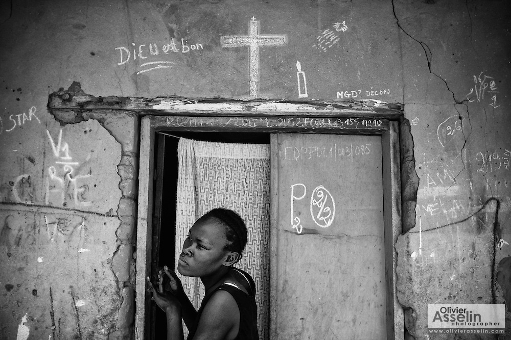 A young woman stands in the doorway of her home after the door was marked with chalk by vaccinators to indicate that occupants were vaccinated against polio in Djambala, Republic of Congo on Wednesday December 8, 2010.