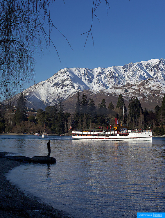 The TSS Earnslaw,  a 1912 Edwardian vintage twin screw steamer on the waters of Lake Wakatipu, Queenstown, New Zealand, with the snow capped mountain range The Remarkables providing a stunning backdrop. Queenstown, New Zealand. 16th July 2011. Photo Tim Clayton