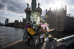 © Licensed to London News Pictures. 22/03/2018. London, UK. Floral tributes on Westminster Bridge in London on the one year anniversary of the Westminster Bridge Terror attack. Lone terrorist, 52-year-old Briton Khalid Masood, killed four people by driving a car at pedestrians then managed to gain entry to the grounds of the Houses of Parliament, killing police officer Keith Palmer. Photo credit: Ben Cawthra/LNP