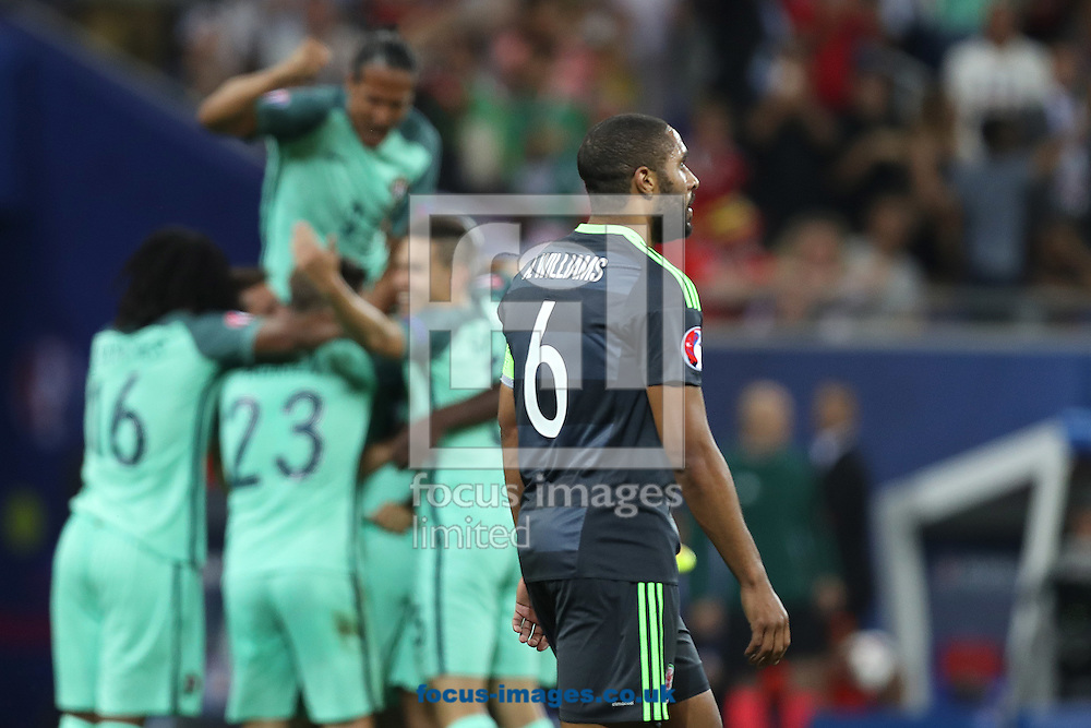 Ashley Williams of Wales looks dejected as the Portugal players celebrate their side&rsquo;s 2nd goal during the UEFA Euro 2016 semi-final match at Stade de Lyons, Lyons<br /> Picture by Paul Chesterton/Focus Images Ltd +44 7904 640267<br /> 06/07/2016
