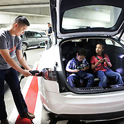 After buckling in his friends Levi and Josiah Dorsey, Steve Ou unplugs his Tesla in a parking garage before driving back to his home in Olympia, Wash. Electric cars charge at the Moda Center arena after the Portland Trailblazers host the Golden State Warriors in an National Basketball Association game in Portland, Ore.