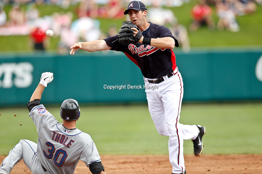 March 5, 2011; Lake Buena Vista, FL, USA; Atlanta Braves short stop Ed Lucas (75) forces out New York Mets catcher Josh Thole (30) during a spring training exhibition game at Disney Wide World of Sports complex.  Mandatory Credit: Derick E. Hingle
