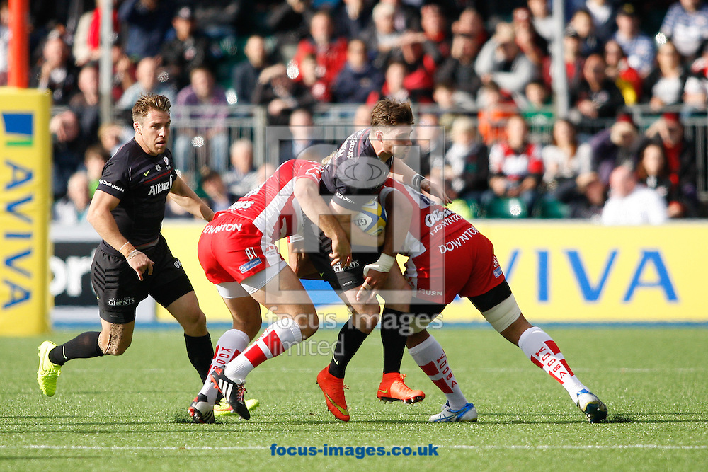 Ben Ransom (C) of Saracens is tackled by Billy Twelvetrees (L) and Ben Morgan (R) of Gloucester during the Aviva Premiership match at Allianz Park, London<br /> Picture by Andrew Tobin/Focus Images Ltd +44 7710 761829<br /> 11/10/2014