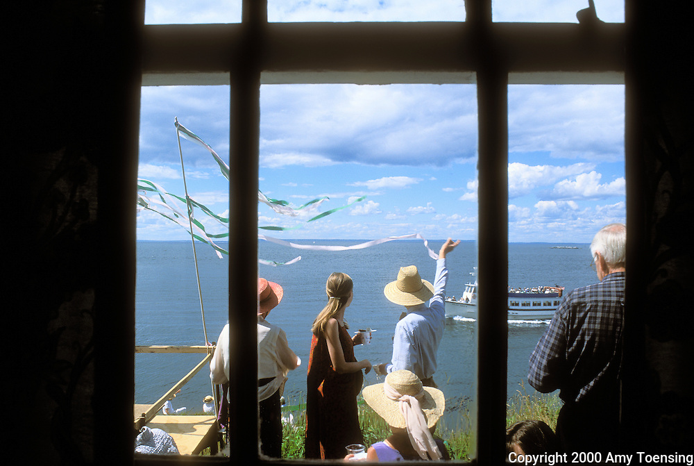 MONHEGAN ISLAND, MAINE - JULY 23: Residents and tourists alike gather for the yearly &quot;Tea by the Sea&quot; party July 23, 2000 on Monhegan Island, Maine. Monhegan Island, home to lobstermen and painters and a popular destination for tourists is twelve miles off the coast of Maine. Ringed by high, dark cliffs, its interior a mix of meadows, marsh and spruce groves, Monhegan is one of just 14 true island communities left off the coast of Maine. The island has a 65 permanent, year-round residents and the population grows to around 200 in the summer, with day-trippers adding several hundred more. (Photo by Amy Toensing) _________________________________________<br /> <br /> For stock or print inquires, please email us at studio@moyer-toensing.com.