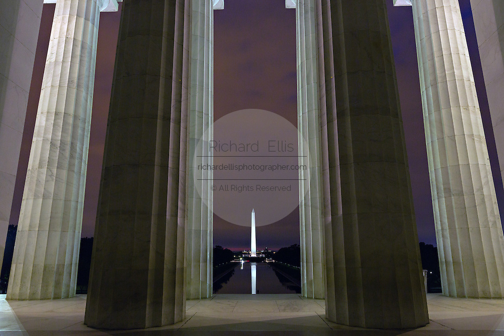 Washington Monument light at dawn framed by the columns of the Lincoln Memorial in Washington, DC.