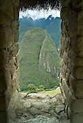 PERU, MACHU PICCHU:  View of the mountains of Machu Picchu and the PeruRail train through a window in the Hut of the Caretaker's House.  Machu Picchu is a pre-Columbian Inca site located 2,430 metres (8,000 ft) above sea level. It was built around 1460 AD but was abandoned as an official site for the Inca rulers a hundred years later, at the time of the Spanish conquest of the Inca Empire.