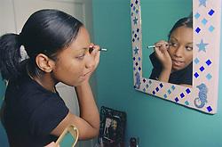 Teenage girl standing in front of mirror applying eye makeup,