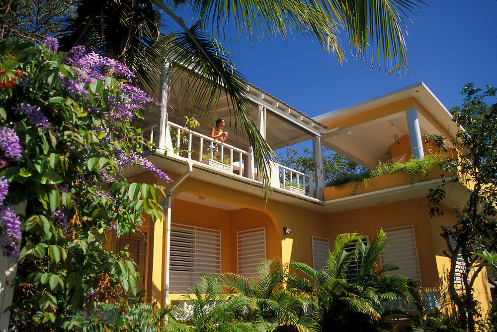 The Crow's Nest Inn, with woman on balcony enjoying piña colada and view; Vieques Island, Puerto Rico.