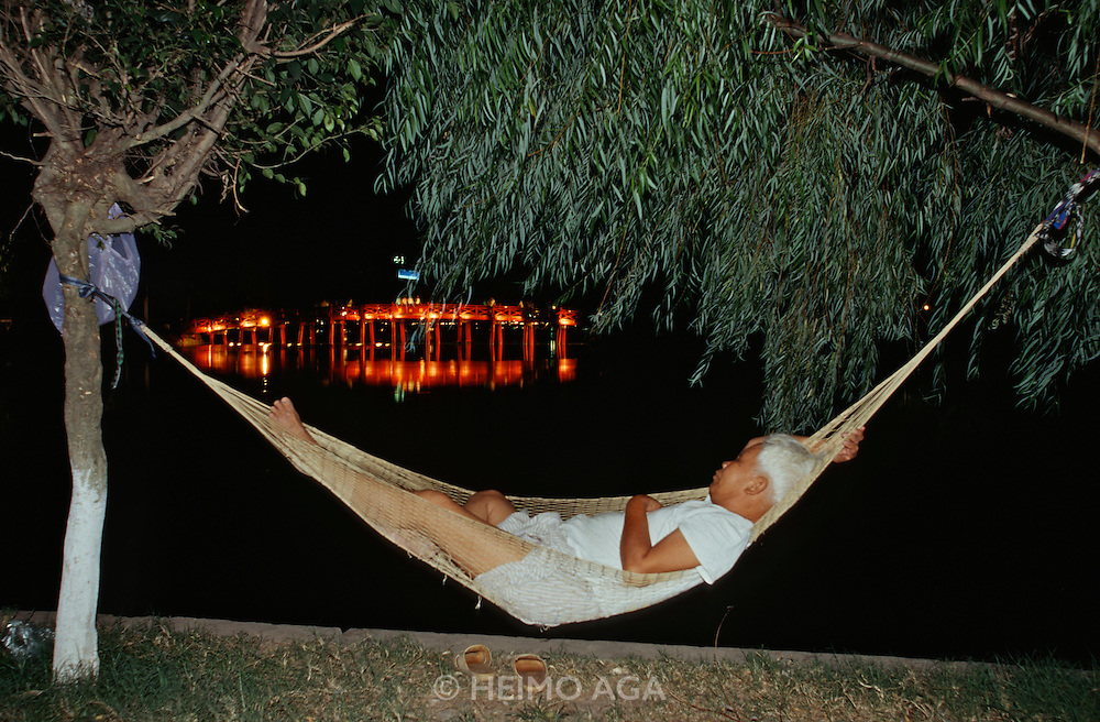 Ho Hoan Kiem (Little Lake). The Huc (Sunbeam Bridge) at night. Old man having a nap in his hammock.