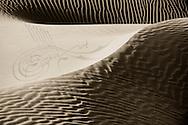 Desert sand dunes with arabic calligraphy.