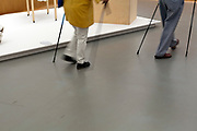 two elderly people with supporting walkingsticks walking