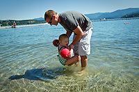 Scott Hyder tries to coach his daughter Chloe into the water at Honeysuckle Beach while on a family outing Sunday, July 25, 2010 in Hayden Lake, Idaho.