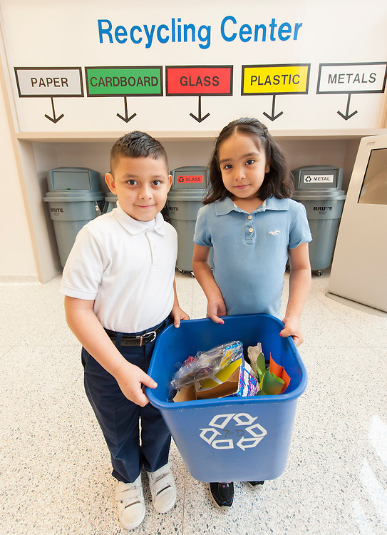 First-graders Isai Rogel, left, and Fatima Carranza prepare to recycle materials from their class at Lewis Elementary school.