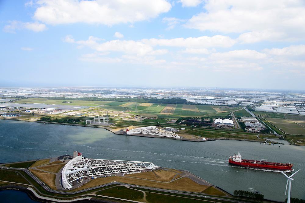 Nederland, Zuid-Holland, Rotterdam, 10-06-2015; Maeslantkering in de Nieuwe Waterweg, gezien naar de Noordzee. Links het Calandkanaal, rechts aan de horizon Hoek van Holland. De stormvloedkering bestaat uit twee deuren die klaar liggen in een dok en welke sluiten bij een waterstand van 3 meter of meer boven NAP. De kering, laatst voltooide onderdeel van Deltawerken, beschermt Rotterdam en achterland bij extreme waterstanden.<br /> The new storm surge barrier (Maeslantkering) in the Nieuwe Waterweg (New Waterway, the entrance to the port of Rotterdam), North Sea at the horizon. In case of storm floods, the two enormous doors will close of the waterway protecting Rotterdam and its hinterland<br /> luchtfoto (toeslag op standard tarieven);<br /> aerial photo (additional fee required);<br /> copyright foto/photo Siebe Swart