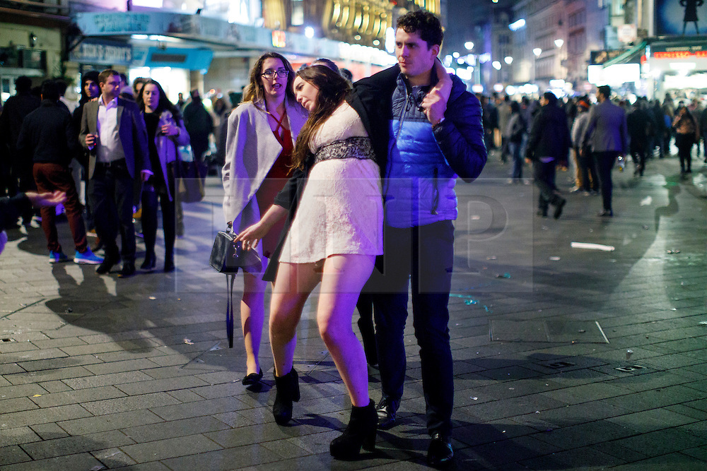 © Licensed to London News Pictures. 01/01/2017. London, UK. An intoxicated reveller feels unwell as people celebrate the New Year in central London during the first hours of 2017 on January 1. Photo credit: Tolga Akmen/LNP