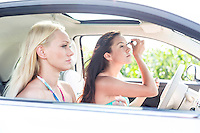 Woman doing make-up with female friend sitting in car