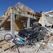 A vehicle and other items are smashed against a home Friday, Oct. 12, 2018 in Mexico Beach. Residents of the small beach town of Mexico Beach began to make their way back to their homes some for the first time after Hurricane Michael made landfall Wednesday.