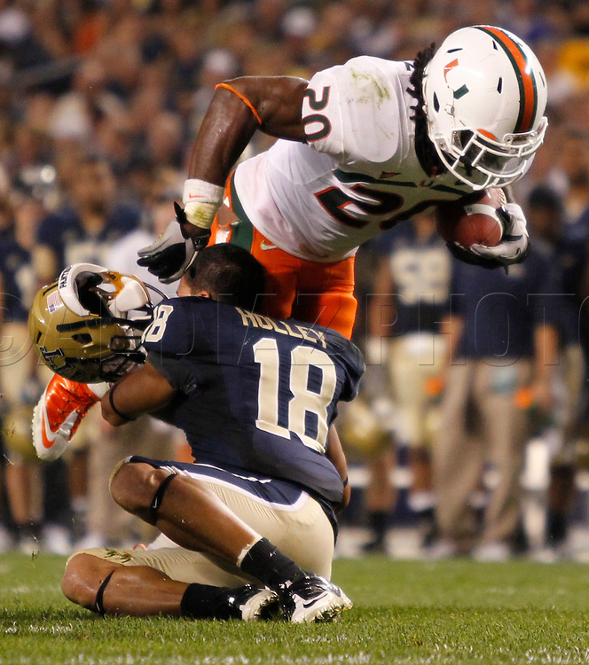 Miami Hurricanes running back Damien Berry (20) knocks the helmet off Pittsburgh Panthers cornerback Jarred Holley (18) in the second quarter. The University of Miami  vs The University of Pittsburgh Panthers at Heinz Field in Pittsburgh, PA, on Thursday, September 23, 2010.