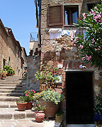 A bike rests against a stone wall on a stairway in Pienza, Italy.