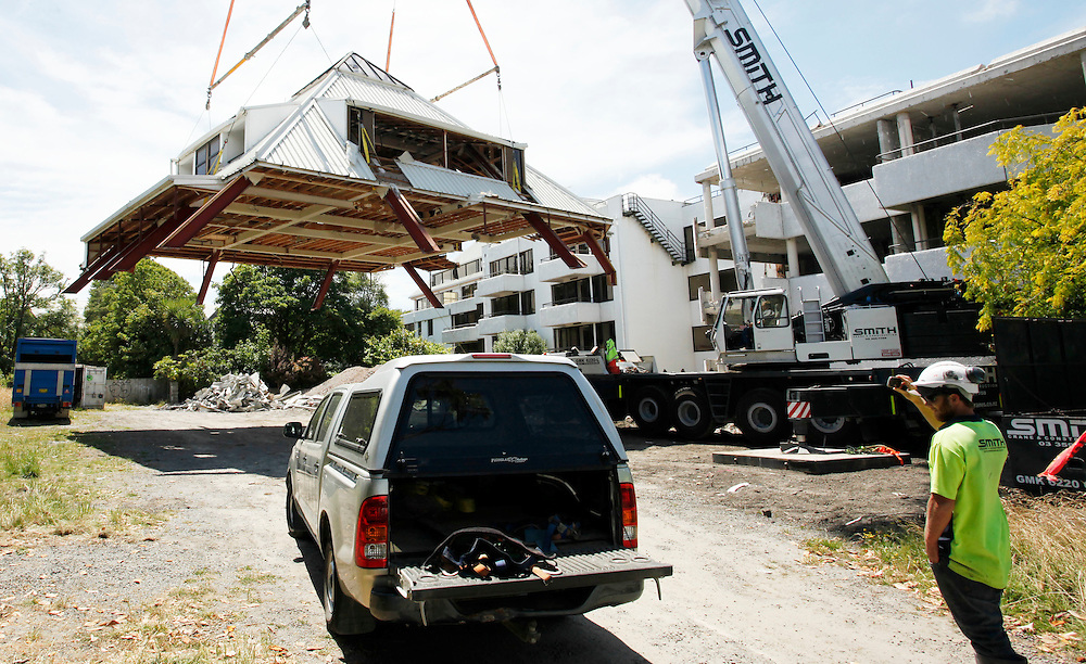 Deconstruction begins on the earthquake damaged Chateau Blanc Apartment Hotel, the roof is being lowered to the ground behind the main building, Christchurch, New Zealand, Thursday, January 12, 2012.  Credit:SNPA / Pam Johnson