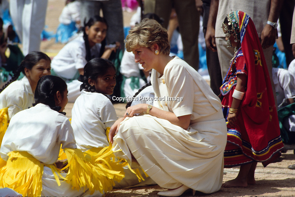 Diana, Princess of Wales bends down to chat with Indian dancers who welcomed her on her arrival  in Hyderabad, India in February, 1992.<br />