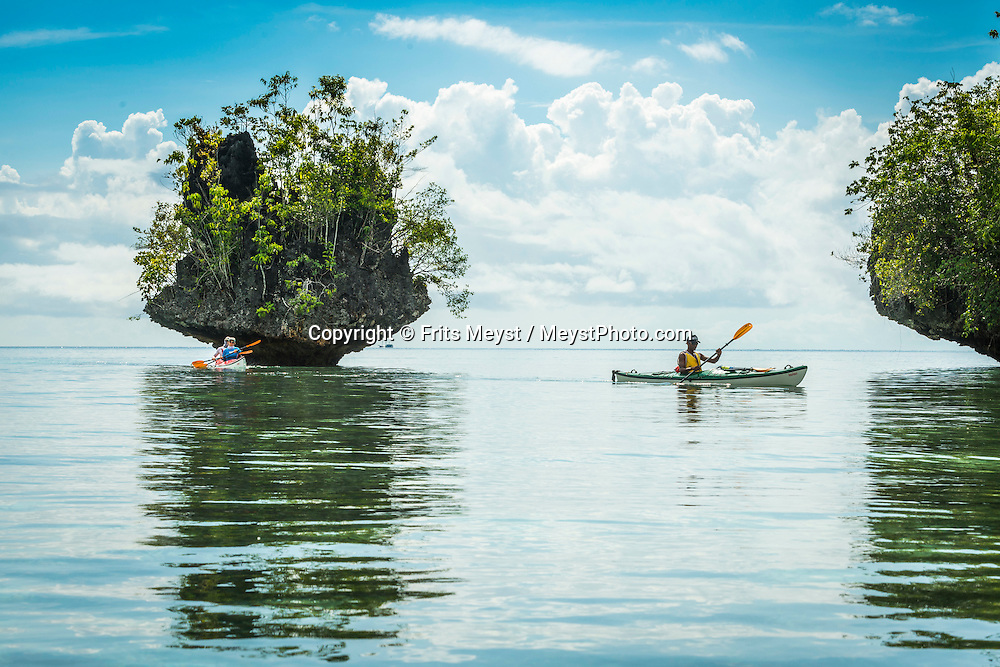 Raja Ampat, West Papua, Indonesia, December 2016. Paddling to Beser Bay we pass mushroom shaped rocks, caves and rock arches. Thousands of small islands fringed by coral reefs and blue water mangroves litter the Raja Ampat archipelago. The turquoise and blue waters are teeming with marine life that forms the livelihood for the local Papuan population. Kayak4conservation is the Raja Ampat Research & Conservation Centre (RARCC) project that supports the locals to develop a community based, sustainable tourism project, inviting visitors to explore their islands by sea kayak with a local guide and experience the culture by staying amongst the local people in traditional style homestays. Photo by Frits Meyst / MeystPhoto.com