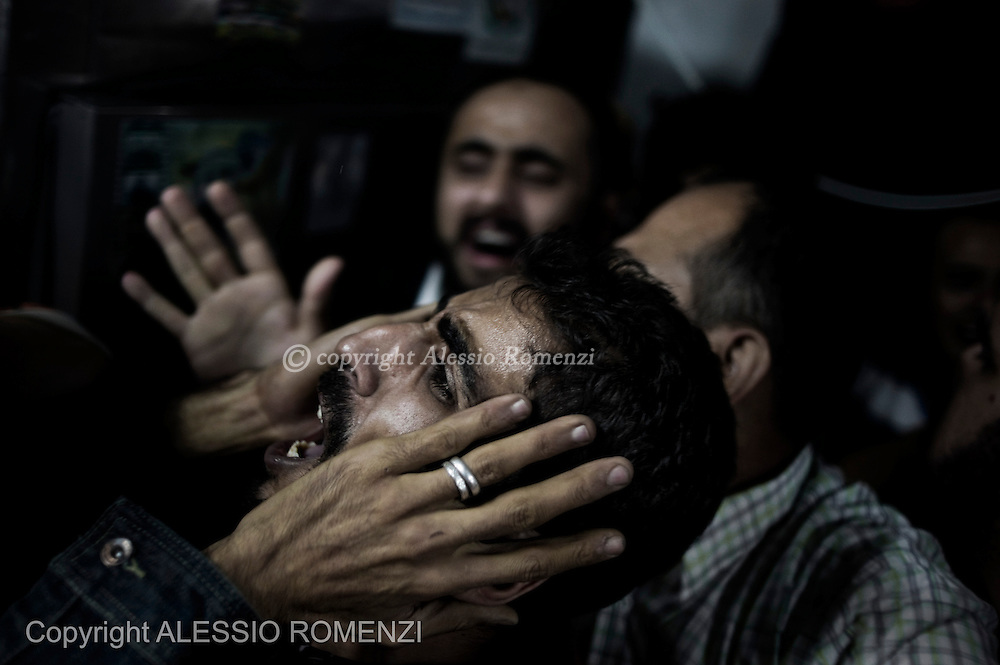Gaza City: Palestinians shout out of rage in the Al Shifa Hospital morgue, after the arrival of the body of Ramez Harb, an Islamic Jihad Militant killed by Israeli airstrike directed to the Al Shoroq building in Gaza city. November 19, 2012. ALESSIO ROMENZI