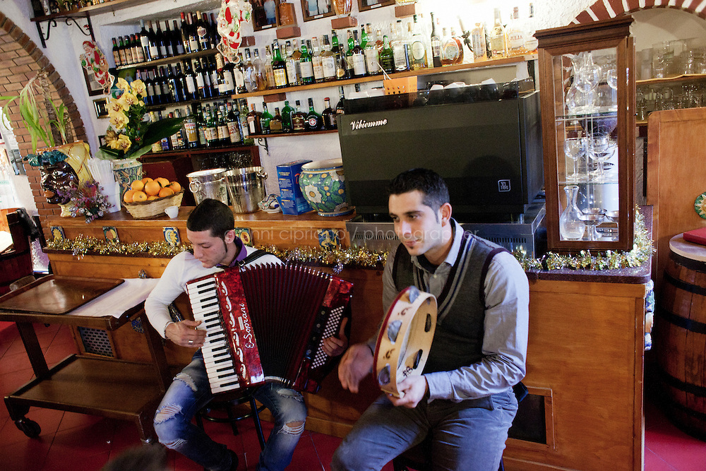 "Taormina, Italy - 6 January, 2013: (L-R) Giuseppe Scionti, 24, and Domenico Maressa, 27, play typical Sicilian music with their accordion and tambourine the ""La Botte"" restaurant during a family lunch to celebrate the Epiphany in Taormina, Italy, on 6 January, 2013. ""La Botte"" restaurant was founded in 1972 by owner Mimma Pellegrino's grandmother Angela. Located about 30 miles north of Catania on the eastern coast of Sicily, Taormina .is a gorgeous seaside town perched on a hilltop with a medieval layout; ancient .ruins; belle époque villas; and sweeping views of the glittering Ionian.Sea, the  Sicilian coastline and, on clear days, the smoking crest of Mount Etna.(about 20  miles away)."