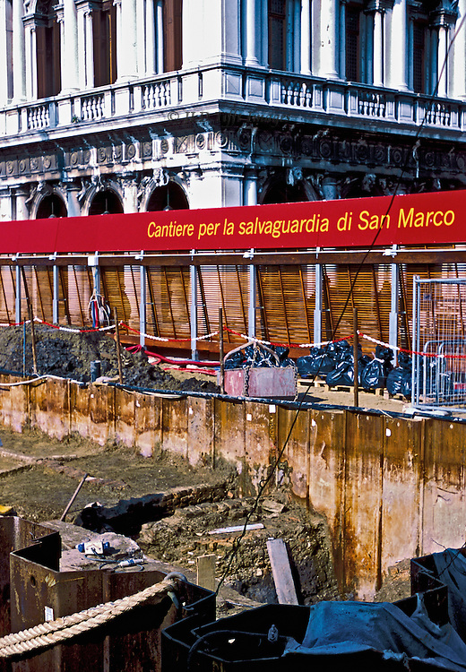 "Tight view of barriers and bulwarks being constructed at the water edge (molo) of the Piazza di San Marco, Venice.  Red banner inscribed: ""Cantiere per la salvaguardia di San Marco"".  Beyond, a corner of the Biblioteca Sansoviniana."