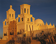 Three-quarter view of Mission of San Xavier del Bac from southeast, golden light of sunrise on wall of adobe, Tucson, Arizona..Subject photograph(s) are copyright Edward McCain. All rights are reserved except those specifically granted by Edward McCain in writing prior to publication...McCain Photography.211 S 4th Avenue.Tucson, AZ 85701-2103.(520) 623-1998.mobile: (520) 990-0999.fax: (520) 623-1190.http://www.mccainphoto.com.edward@mccainphoto.com.
