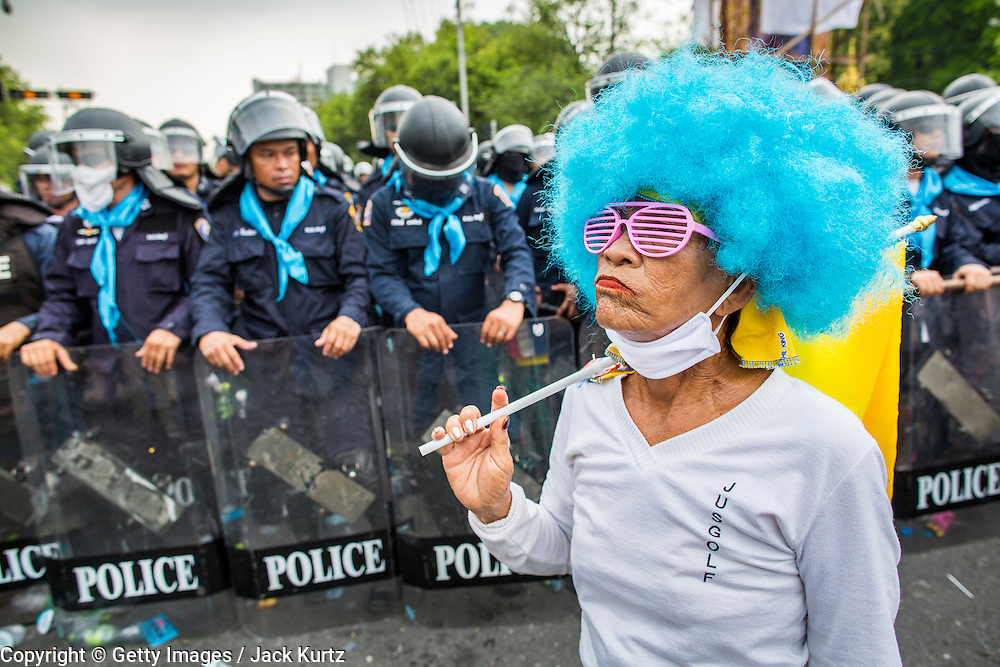 24 NOVEMBER 2012 - BANGKOK, THAILAND: An anti government protester walks past Thai riot police during a large anti government, pro-monarchy, protest  on November 24, 2012 in Bangkok, Thailand. The Siam Pitak group, which sponsored the protest, cited alleged government corruption and anti-monarchist elements within the ruling party as grounds for the protest. Police used tear gas and baton charges againt protesters.       PHOTO BY JACK KURTZ