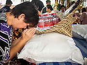 "26 AUGUST 2013 - BANGKOK, THAILAND:     A woman prays over rice she is donating to the Poh Teck Tung Foundation for Hungry Ghost Month in Bangkok. Poh Teck Tung operates hospitals and schools and provides assistance to the poor in Thailand. The seventh lunar month (August - September in 2013) is when the Chinese community believes that hell's gate will open to allow spirits to roam freely in the human world for a month. Many households and temples will hold prayer ceremonies throughout the month-long Hungry Ghost Festival (Phor Thor) to appease the spirits. During the festival, believers will also worship the Tai Su Yeah (King of Hades) in the form of paper effigies which will be ""sent back"" to hell after the effigies are burnt.    PHOTO BY JACK KURTZ"