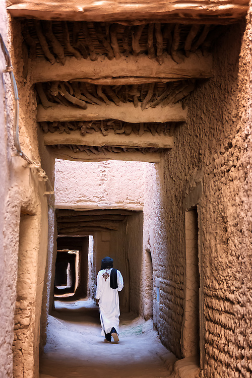 Traditional dressed man walks through an arch way inside a kasbah.